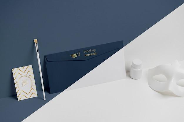 Alto angolo di invito di carnevale minimalista in busta con maschera e pennello