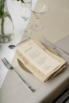 Angolo alto del mock-up del menu primaverile sul piatto con posate e bicchieri
