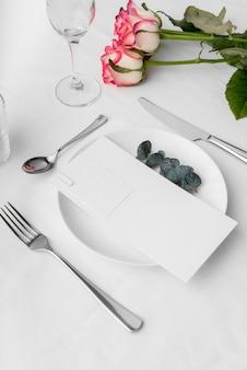 Angolo alto del mock-up del menu primaverile sul piatto con i fiori