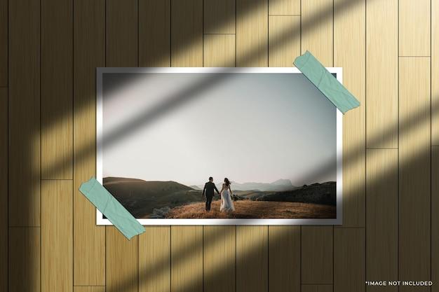 Modello di foto con cornice di carta orizzontale con sovrapposizione di ombre della finestra e sfondo di legno