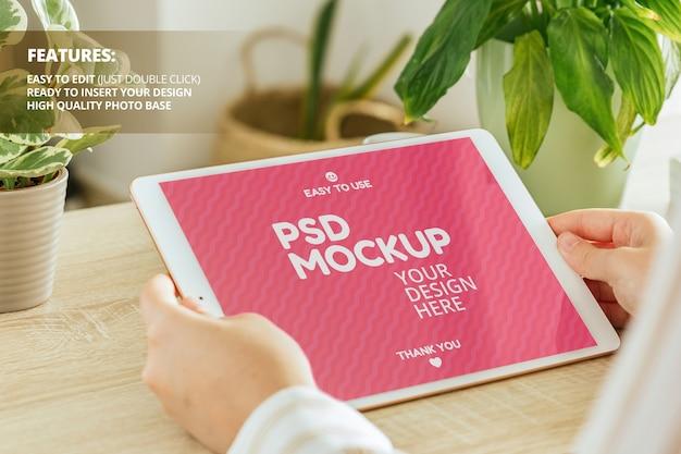 Mockup di tablet orizzontale tenuto da donna