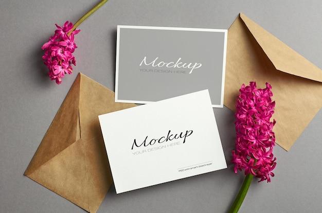 Mockup di biglietto d'invito, lati anteriore e posteriore con buste e fiori freschi di giacinto