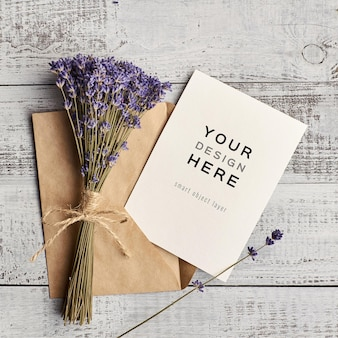 Mockup di carta di invito con busta e bouquet di fiori di lavanda