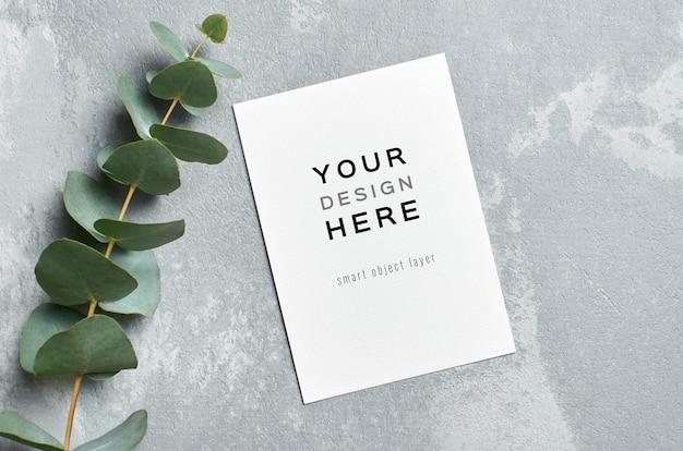 Mockup di carta di invito con ramoscelli di eucalipto freschi su grigio