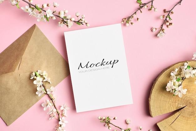 Mockup di invito o biglietto di auguri con tronco tagliato, busta e ramoscelli di ciliegio con fiori