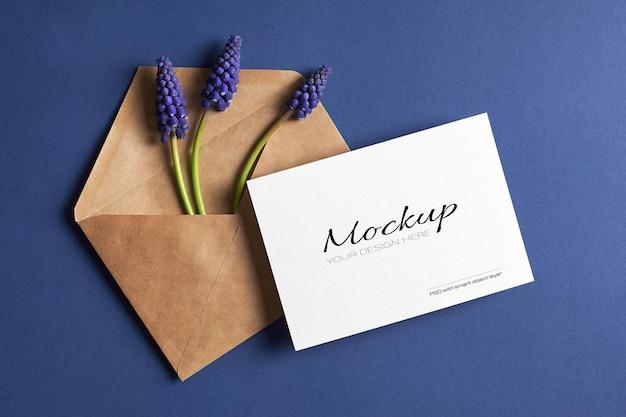 Mockup di invito o biglietto di auguri con busta e fiori muscari blu