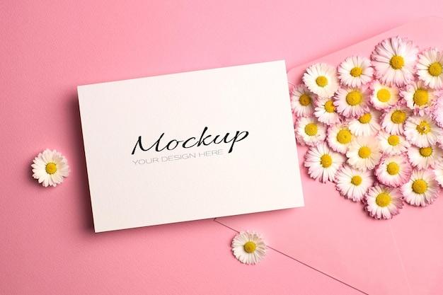 Modello di invito o biglietto di auguri con busta e fiori margherita su rosa