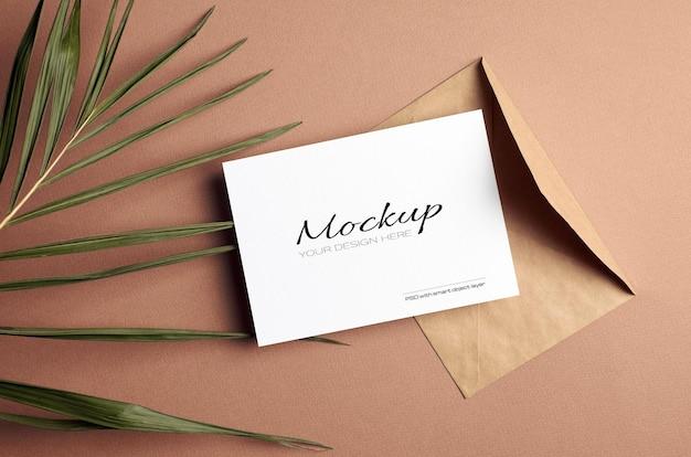 Modello di invito o biglietto di auguri con busta e foglia di palma naturale secca su sfondo beige