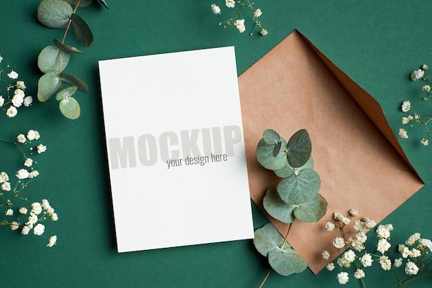 Modello di invito o biglietto di auguri con busta, eucalipto e ramoscelli di ipsofila su verde