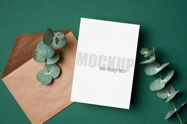 Modello di invito o biglietto di auguri con busta e ramoscello di eucalipto su verde