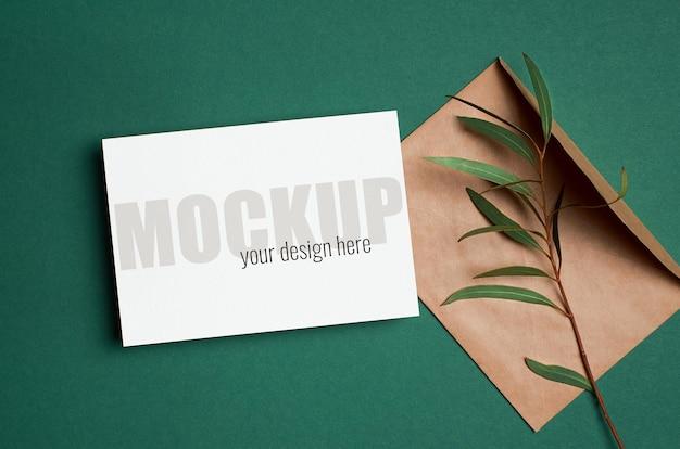 Modello di invito o biglietto di auguri con busta e ramoscello di eucalipto su verde Psd Premium