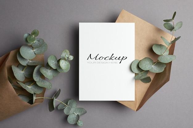 Modello di invito o biglietto di auguri con busta e ramoscelli di eucalipto su grigio