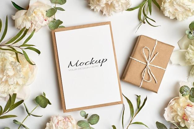 Modello di invito o biglietto di auguri con busta, confezione regalo e fiori di peonia bianca con ramoscelli di eucalipto