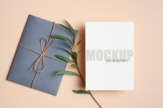 Modello di invito o biglietto di auguri con busta e ramoscello di eucalipto verde
