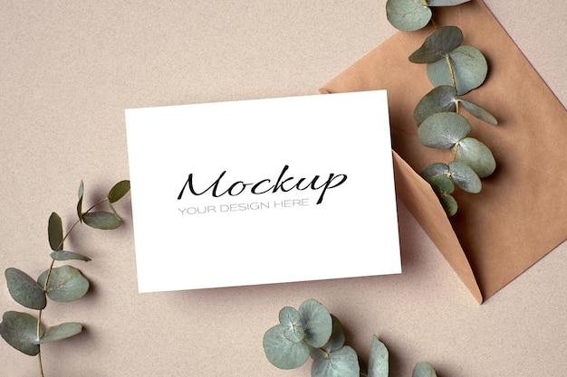 Modello di invito o biglietto di auguri con busta e ramoscelli di eucalipto verde