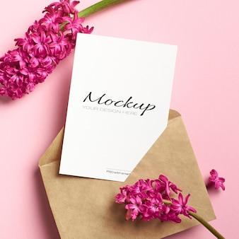 Mockup di invito o biglietto di auguri con busta e fiori di giacinto sul rosa
