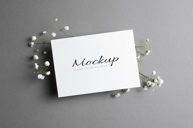 Modello di invito o biglietto di auguri con busta e ramoscelli di ipsofila su grigio