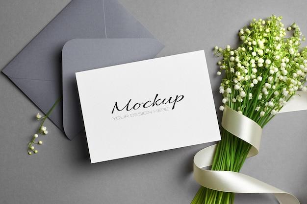 Modello di invito o biglietto di auguri con busta e bouquet di fiori di mughetto con nastro