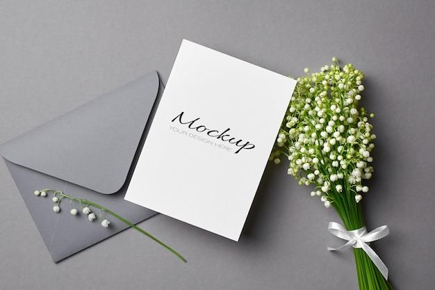 Modello di invito o biglietto di auguri con busta e bouquet di fiori di mughetto