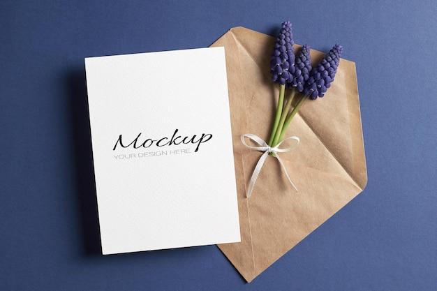 Modello di invito o biglietto di auguri con busta e fiori muscari blu primaverili