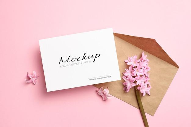 Mockup di invito o biglietto di auguri con busta e fiori di giacinto primaverile sul rosa