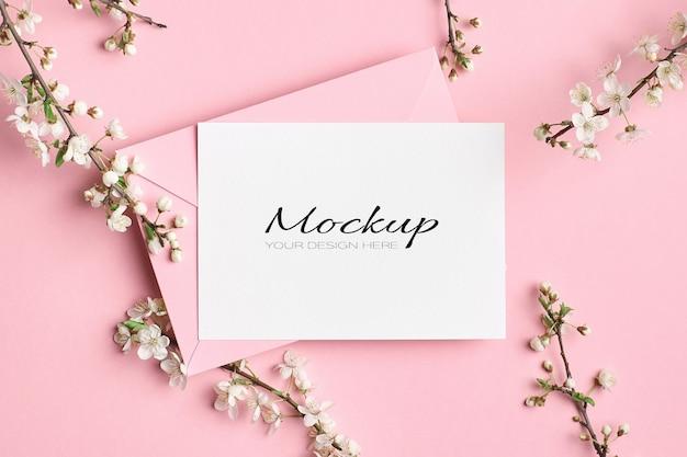 Modello di invito o biglietto di auguri con busta e ramoscelli di albero primaverile con fiori su rosa
