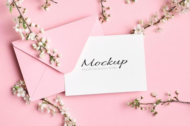Mockup di invito o biglietto di auguri con busta e ramoscelli di albero primaverile con fiori