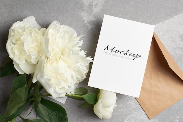 Modello di invito o biglietto di auguri con busta e fiori di peonia bianca su grigio