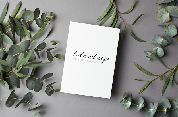 Modello di invito o biglietto di auguri con ramoscelli di eucalipto su grigio