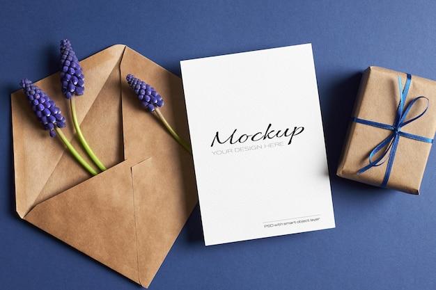 Modello di invito o biglietto di auguri con confezione regalo, busta e fiori di muscari blu