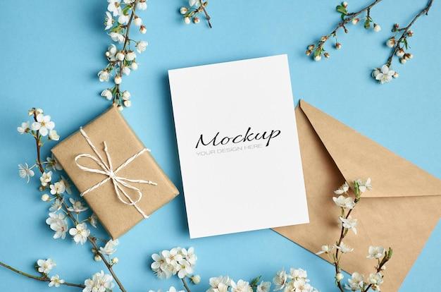 Mockup di invito o biglietto di auguri con scatola regalo, busta e ramoscelli fioriti di ciliegio