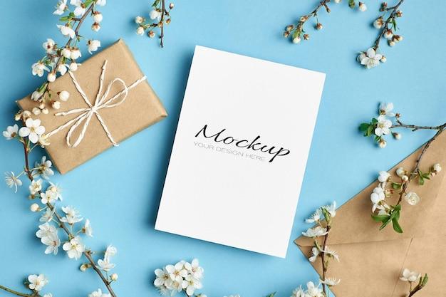 Mockup di invito o biglietto di auguri con scatola regalo, busta e ramoscelli di ciliegio con fiori