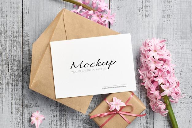 Mockup di invito o biglietto di auguri con confezione regalo e fiore di giacinto rosa