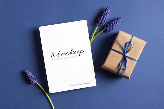 Modello di invito o biglietto di auguri con confezione regalo e fiori muscari blu primaverili