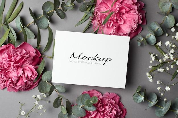 Modello di invito o biglietto di auguri con fiori di peonia, ipsofila e ramoscelli di eucalipto