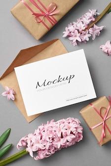Mockup di invito o biglietto di auguri con busta rosa, confezione regalo e fiori di giacinto