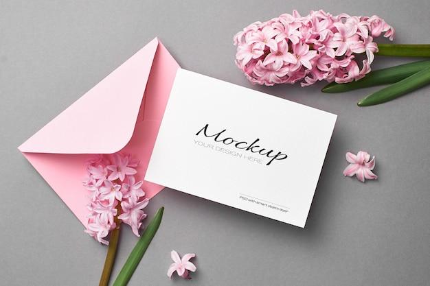 Mockup di invito o biglietto di auguri con busta rosa e fiori di giacinto