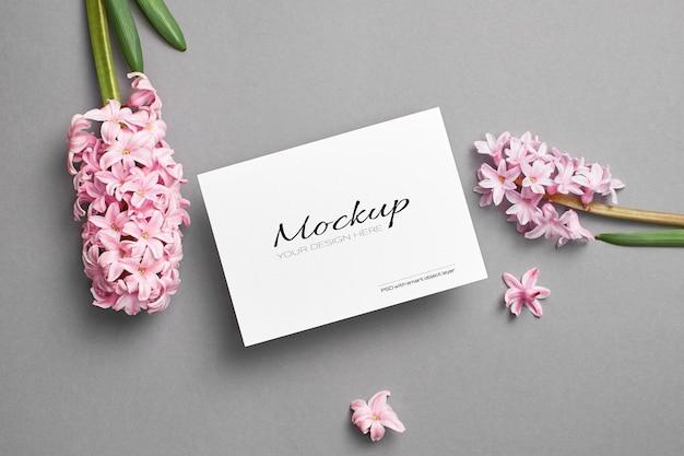 Mockup di invito o biglietto di auguri con fiori di giacinto rosa su grigio