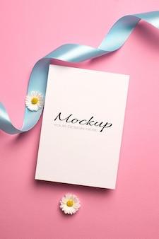 Modello di invito o biglietto di auguri con nastro e fiori margherita su rosa