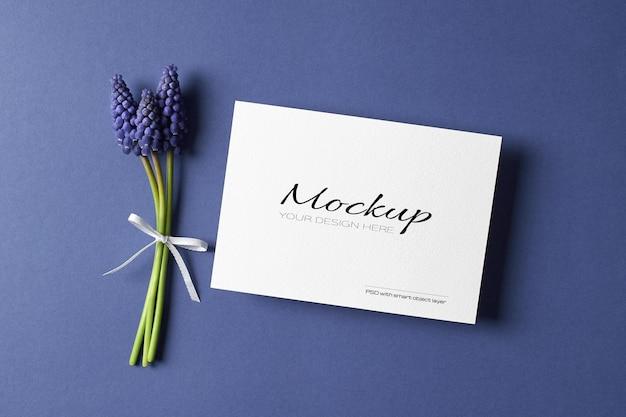 Mockup di invito o biglietto di auguri con fiori muscari blu primaverili