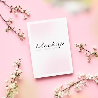 Mockup di invito o biglietto di auguri con ramoscelli di fiori di ciliegio primaverile