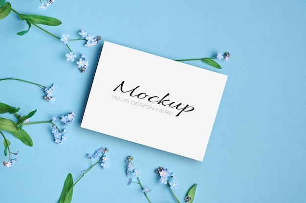 Modello di invito o biglietto di auguri con fiori primaverili del nontiscordardime su blu