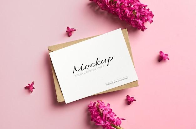 Mockup di invito o biglietto di auguri con fiori di giacinto primaverile su sfondo di carta rosa