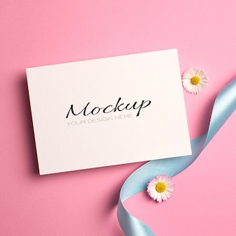 Modello di invito o biglietto di auguri con nastro turchese e fiori margherita su rosa
