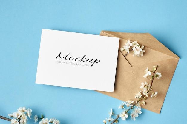 Mockup fisso di invito o biglietto di auguri con busta e fiori di ciliegio