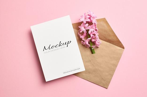 Mockup stazionario di invito o biglietto di auguri con busta e fiori di giacinto rosa