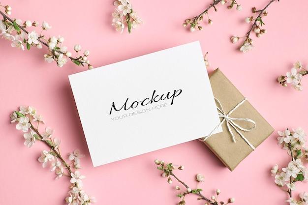 Mockup stazionario di invito o biglietto di auguri con confezione regalo e ramoscelli di ciliegio con fiori