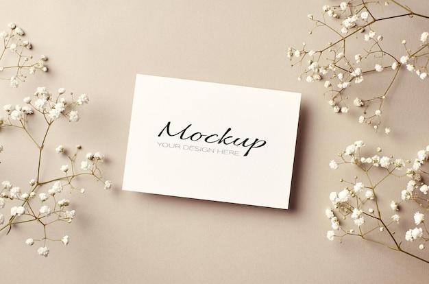 Mockup stazionario di invito o biglietto di auguri con fiori di hypsophila bianchi