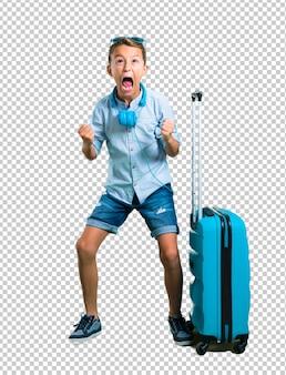 Kid con occhiali da sole e cuffie che viaggiano con la sua valigia infastidito arrabbiato in gesto furioso