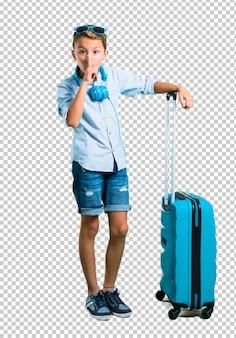 Bambino con occhiali da sole e cuffie che viaggiano con la sua valigia mostrando un segno di chiusura m